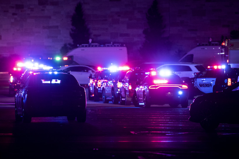 Red and blue lights from police cars illuminate a dark parking lot