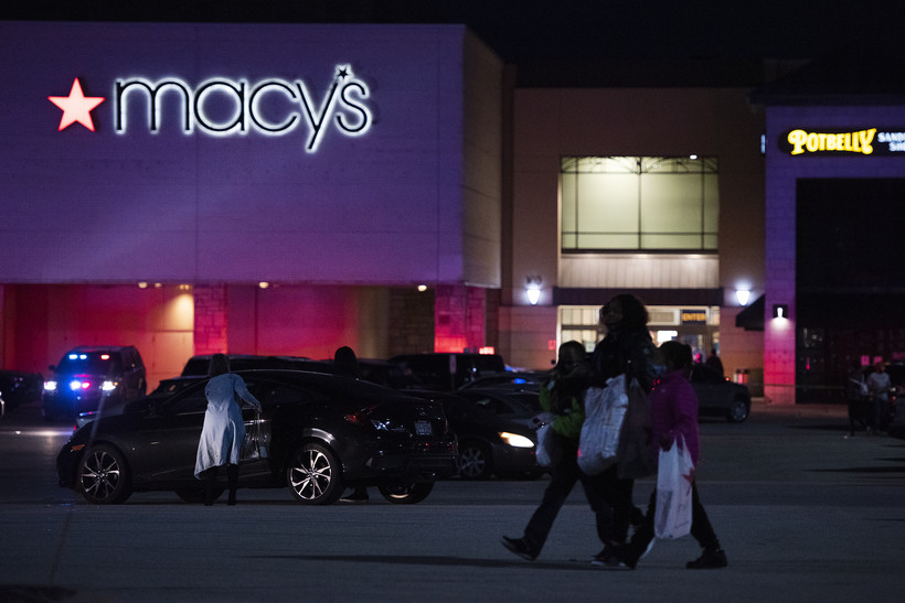Three people with white shopping bags pass through a dark parking lot in front of a Macy's