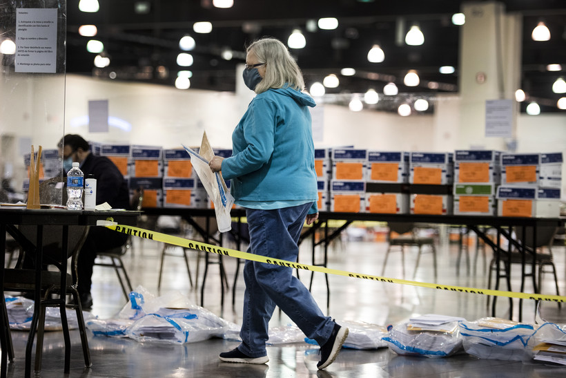 A woman walks past boxes and bags containing ballots