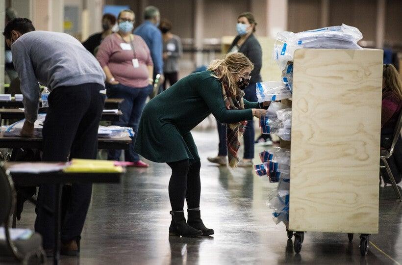A woman reaches into a wooden cart to grab a bag containing ballots