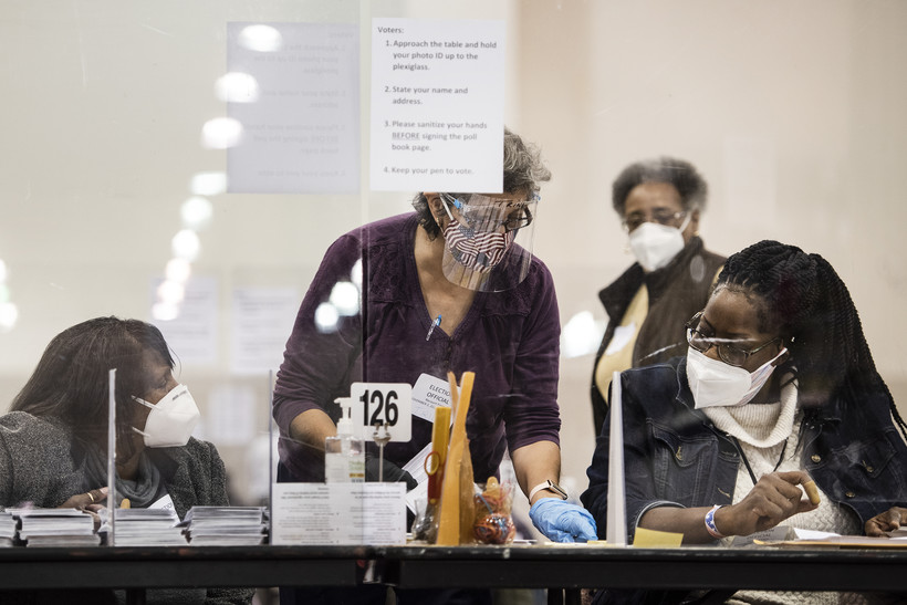 A woman in a US flag face mask and face shield speaks to two other election observers