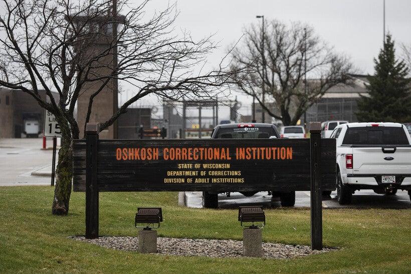 "A sign says ""Oshkosh Correctional Institution"" in orange letters"
