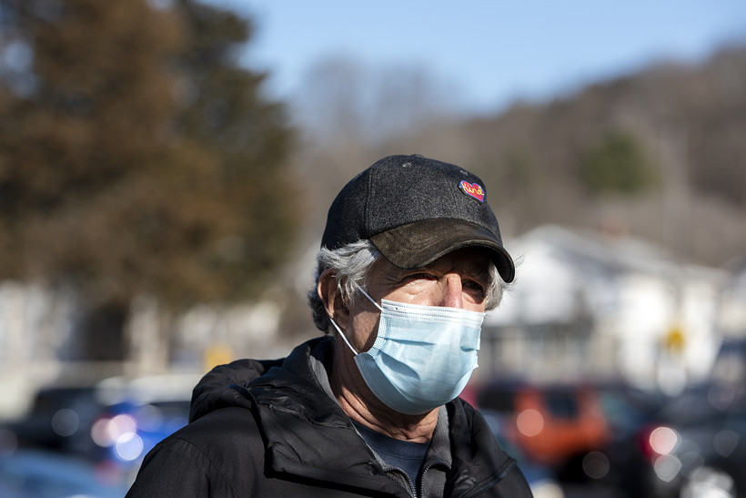 A man in a cap and face mask stands outside
