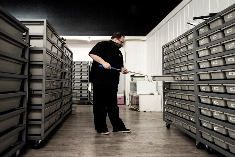 A man pulls out a bin from shelf containing many small gray bins