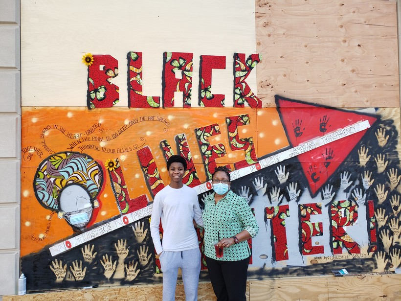 Batenga Obuseh and her 15-year-old son, Kiyem Obuseh, work on one of the State Street murals covering the Overture Center for the Arts.