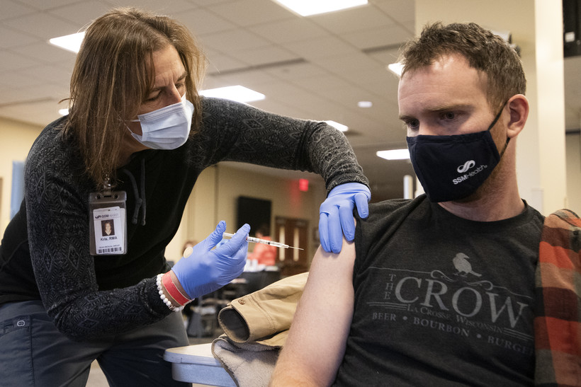 A nurse wears blue gloves as she gives a vaccine to a man with rolled up sleeves
