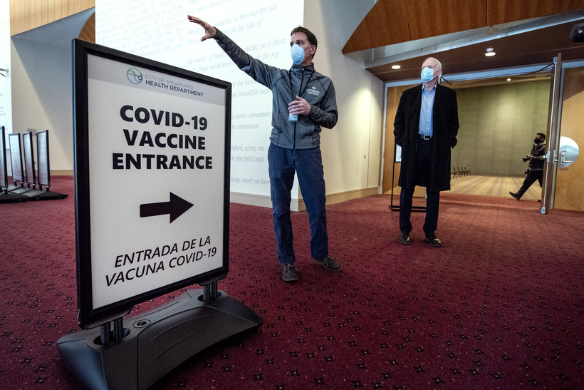 "Two men in face masks stand by a sign that says ""COVID-19 Vaccine Entrance"""