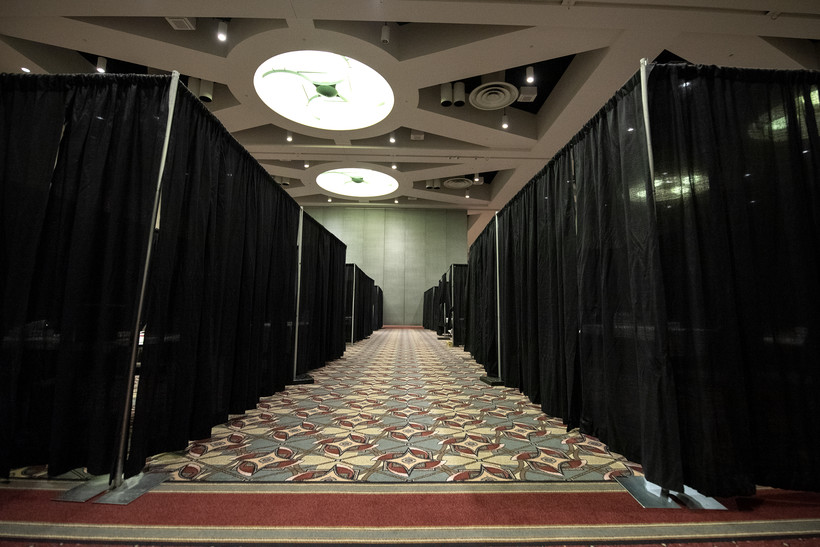 Black curtains hang in a large conference room to section off spaces for vaccine administration