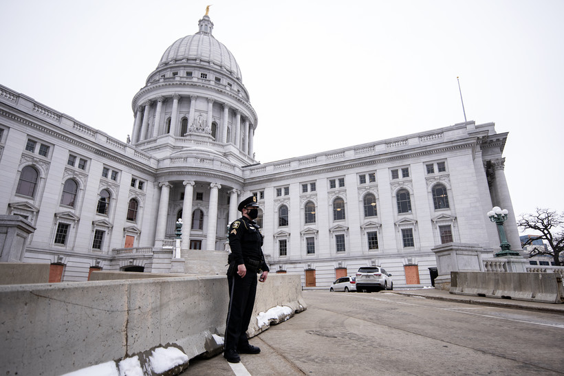 a police officer in uniform stands in front of a barrier at the Wisconsin State Capitol