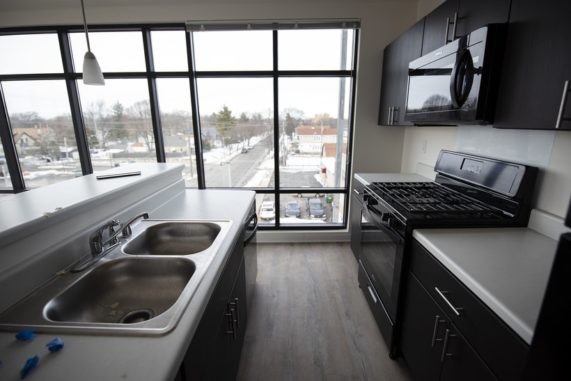 White countertops and black appliances create a small kitchen area that is surrounded by large windows taking up nearly the entire wall
