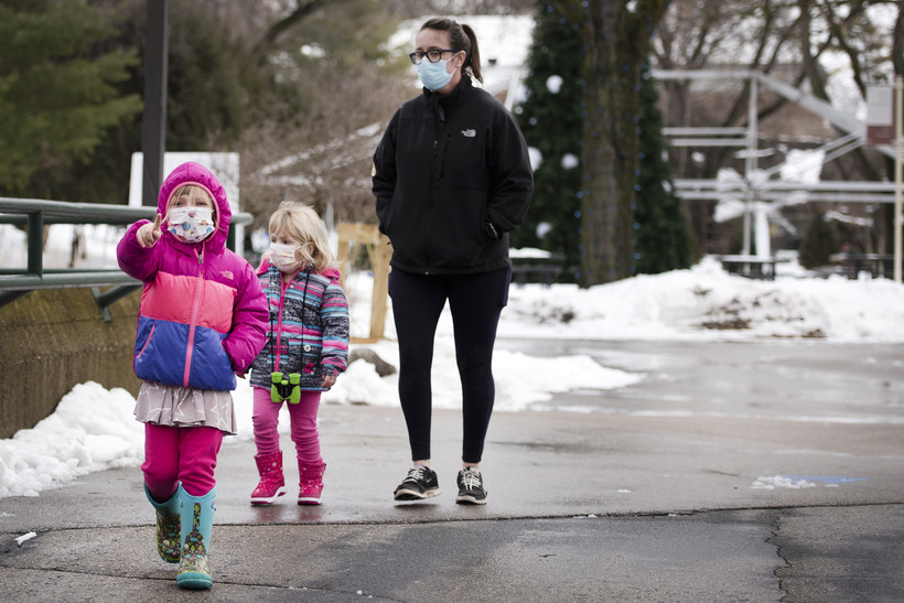 Two children walk with an adult, all in face masks, at the zoo