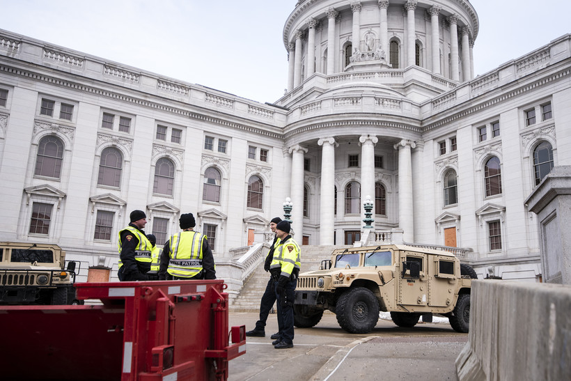 Police in neon vests stand near a national guard vehicle outside the capitol