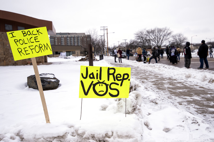 """two small yellow signs say """"I back police reform"""" and """"Jail Rep. Vos"""""""