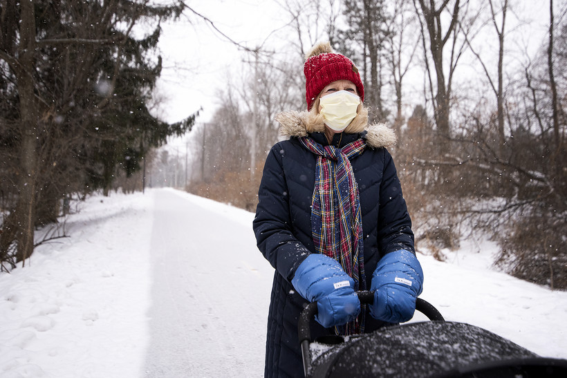 A woman in a face mask and winter gear walks outside in the snow