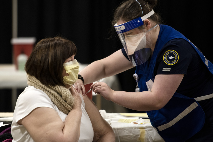 A woman in a face mask looks up at a nurse as she receives her covid-19 vaccine