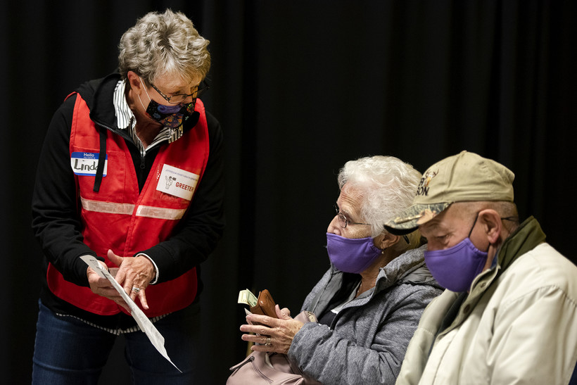 a greeter presents information to a couple sitting in an observation area
