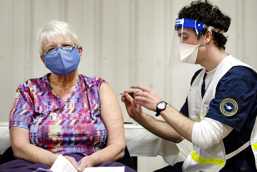 a woman in a purple mask has a rolled up sleeve as a student nurse gives her the covid-19 vaccine