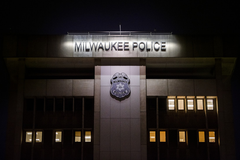 """The words """"Milwaukee Police"""" on the side of a building are illuminated by a line of light at nighttime"""