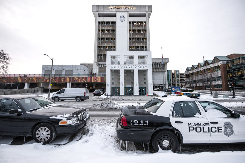 Two Milwaukee police vehicles are parked on a snowy street. The Milwaukee police department is in the background.