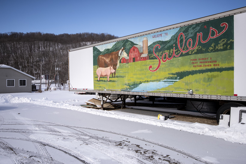 """A large trailer has a farm scene and the words """"Sailer's Food Market and Meat Processing"""" painted on the side of it."""