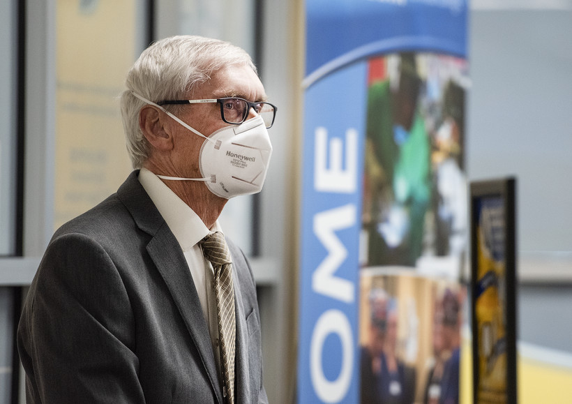 Gov. Tony Evers wears a face mask as he looks at the reporters at the press conference