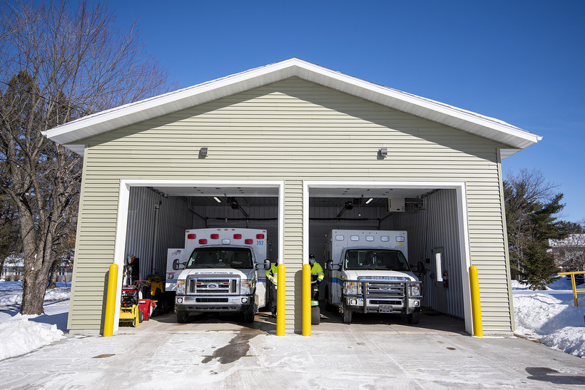 Two ambulances are parked inside of a small garage with the doors rolled up.