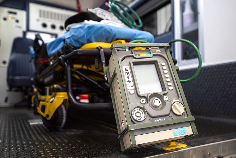A ventilator with a screen and many buttons and knobs is placed in the back of an ambulance.