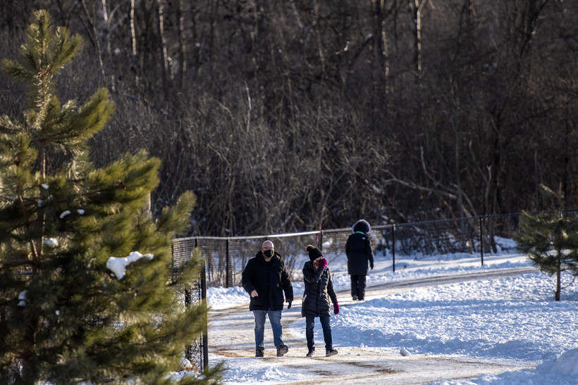 People walk on a snowy path outdoors.
