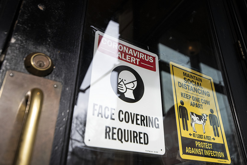 """A sign on a clear glass door says """"Face Covering Required."""""""