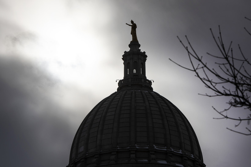 """A silhouetted """"Wisconsin"""" statue is seen in front of dark clouds."""
