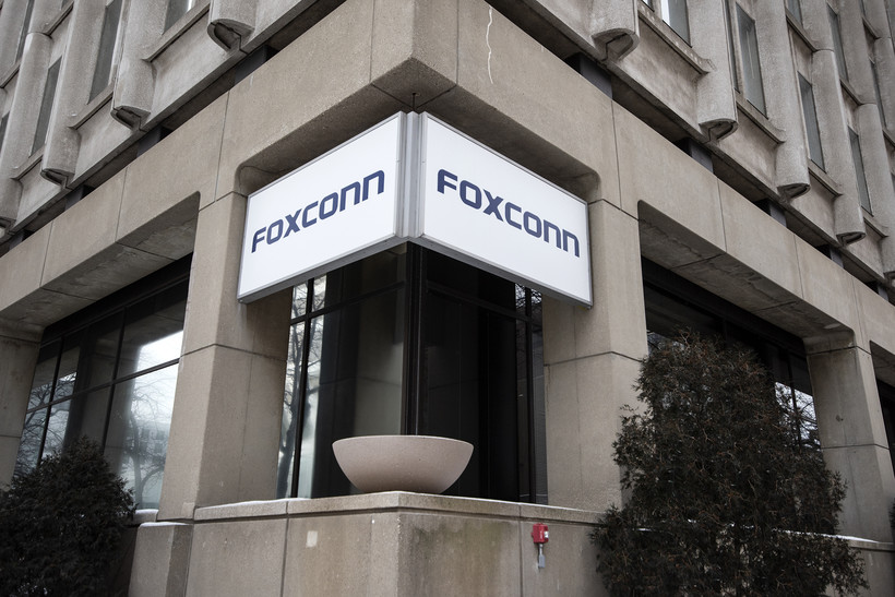 """A white sign with the word """"Foxconn"""" on it hangs on a concrete building."""