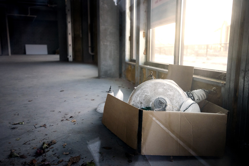A cardboard box with various light fixtures inside sits on the concrete floor of a vacant room.