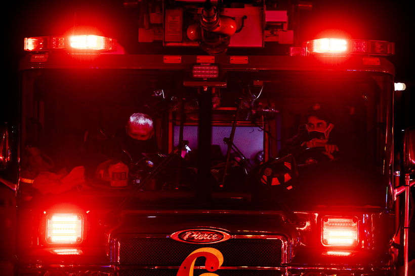Four bright red lights glow into the night from a firetruck where firefighters are sitting.