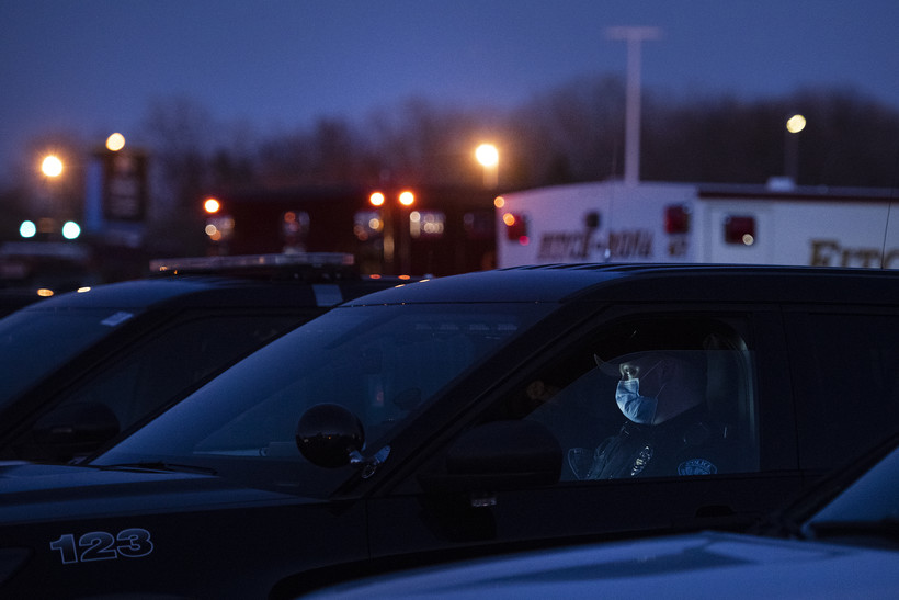 A police officer in a mask sits in a vehicle as the sky goes dark.