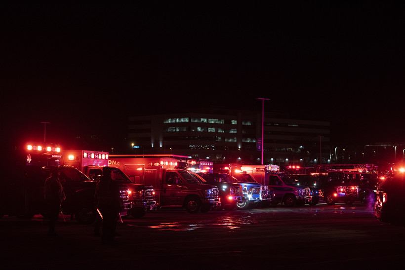 Several lights from emergency vehicles fill the dark night sky with red light.