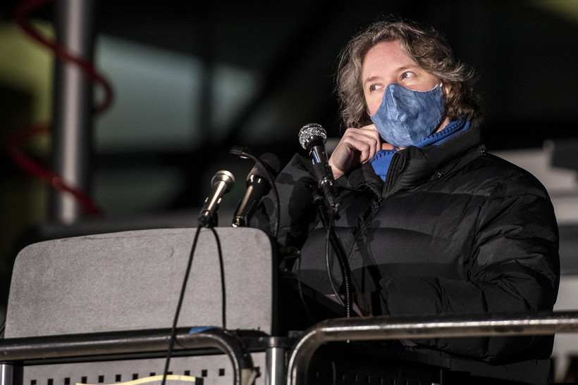 A woman removes a face mask as she approaches the lectern.