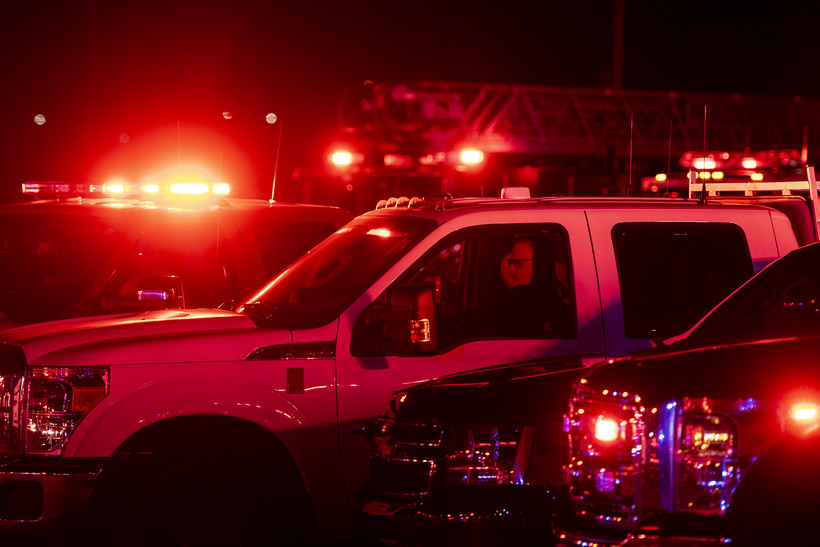 A white truck is lit up with red lights as a man sits inside.