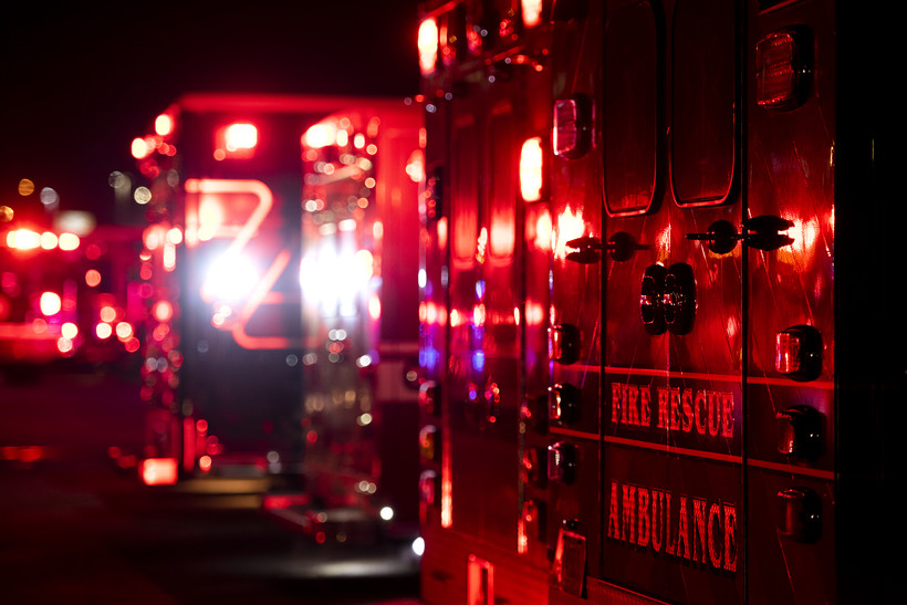 """The back of an ambulance displays the words """"fire rescue ambulance."""""""