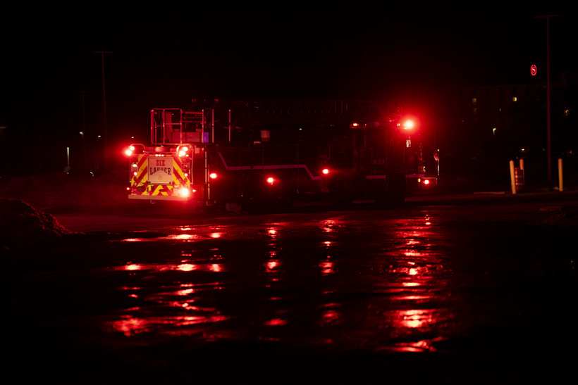 A dark night sky surrounds a firetruck with red lights on. Ice and water on the pavement glow with a reflection.