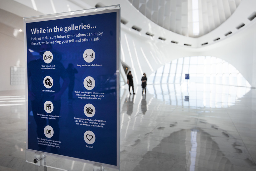 """A blue sign is seen in the front of the museum begins with """"While in the galleries..."""" and then explains COVID-19 safety rules."""