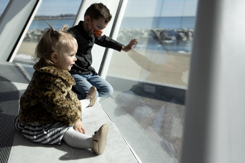 Sun shines on two children as they look out of a large window.