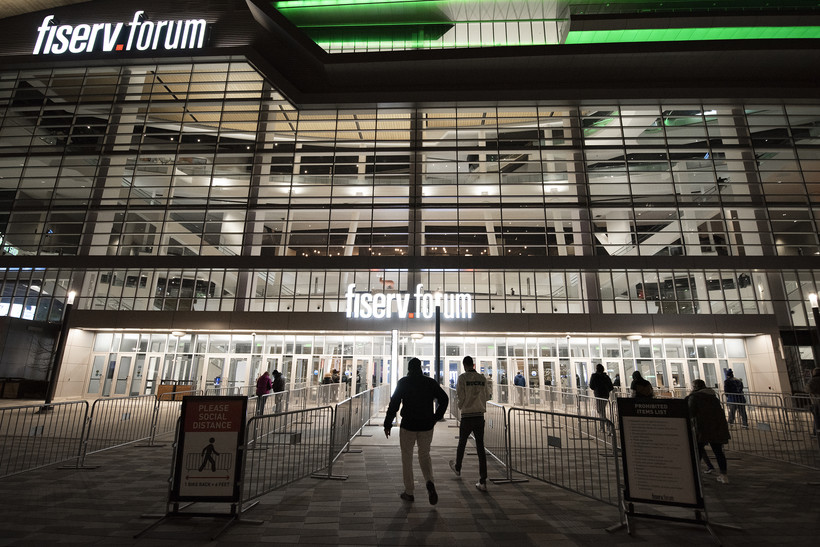 People enter the Fiserv Forum at night