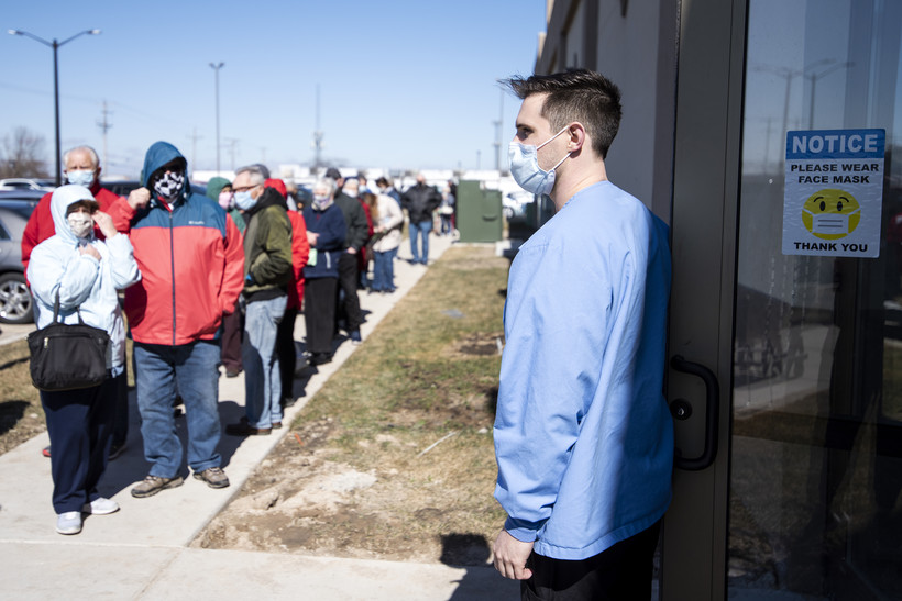 A line of people in jackets and face masks wait to enter a door held open by a medical worker.