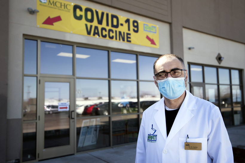 "A man in a face mask stands by a yellow and red sign that says ""COVID-19 Vaccine"""