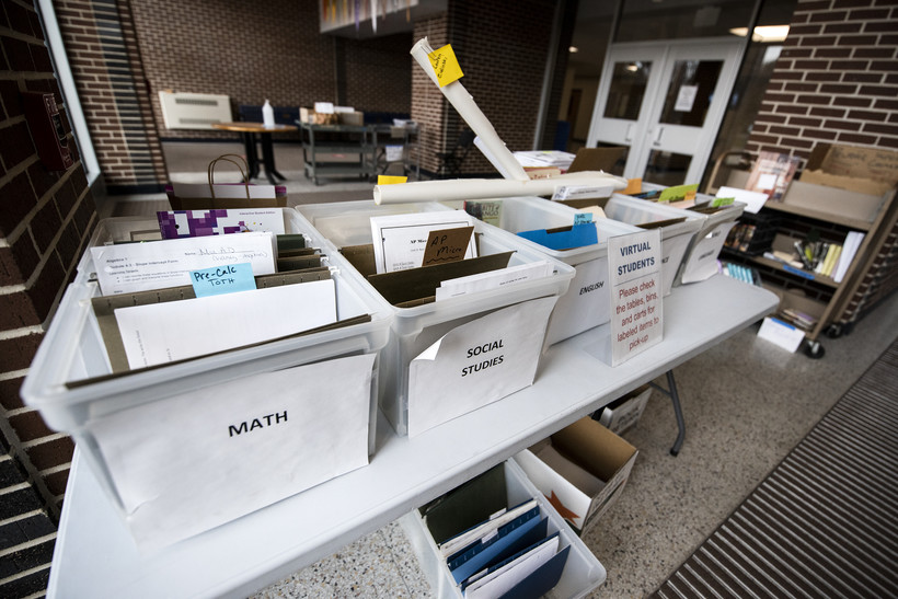 Boxes of papers in folders are placed on tables in a school lobby.