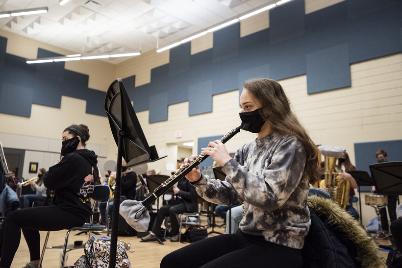 A student wears a face mask as she plays the clarinet.