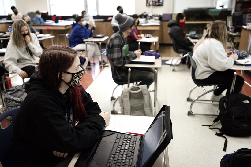A student with a laptop on her desk wears a face mask with other students in class.