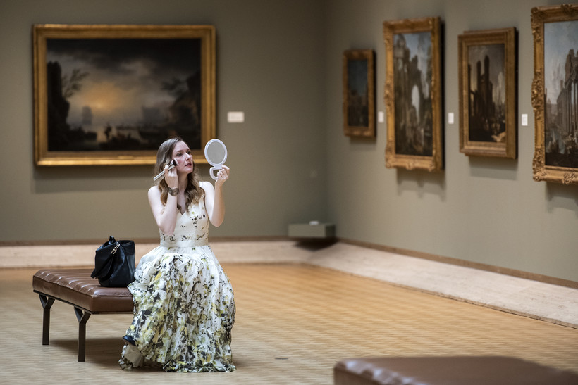 A woman in a white gown sits on a bench as she holds a makeup brush and a mirror.