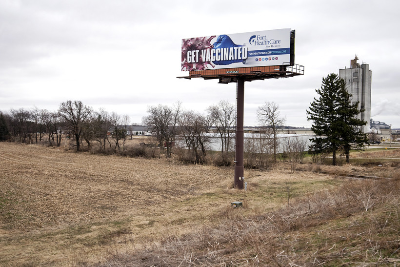 """A billboard shows the words """"Get Vaccinated."""""""