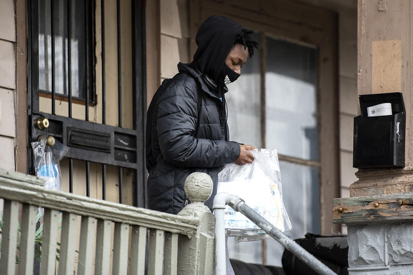 A person carries plastic bags as he walks away from a house's front door.
